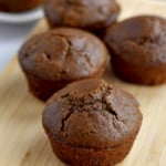 Four gluten free double chocolate muffins on a wood cutting board with more muffins in the background.