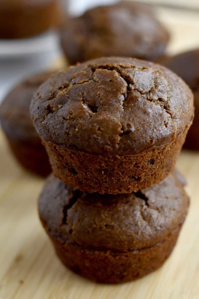 A stack of two gluten free double chocolate muffins on a wood cutting board with more muffins in the background.
