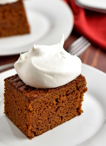 A slice of gluten free gingerbread cake, topped with whipped topping, on a small white plate with a fork and more cake in the background.