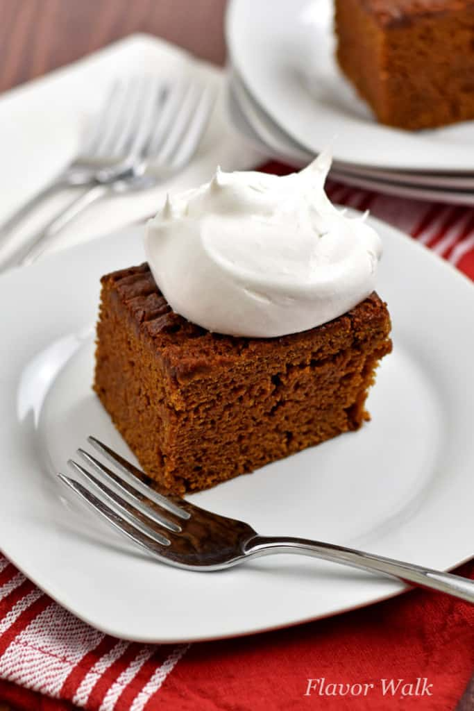 A piece of gluten free gingerbread cake, topped with whipped topping, and a fork on a small white plate. Additional forks, plates, and cake in the background.