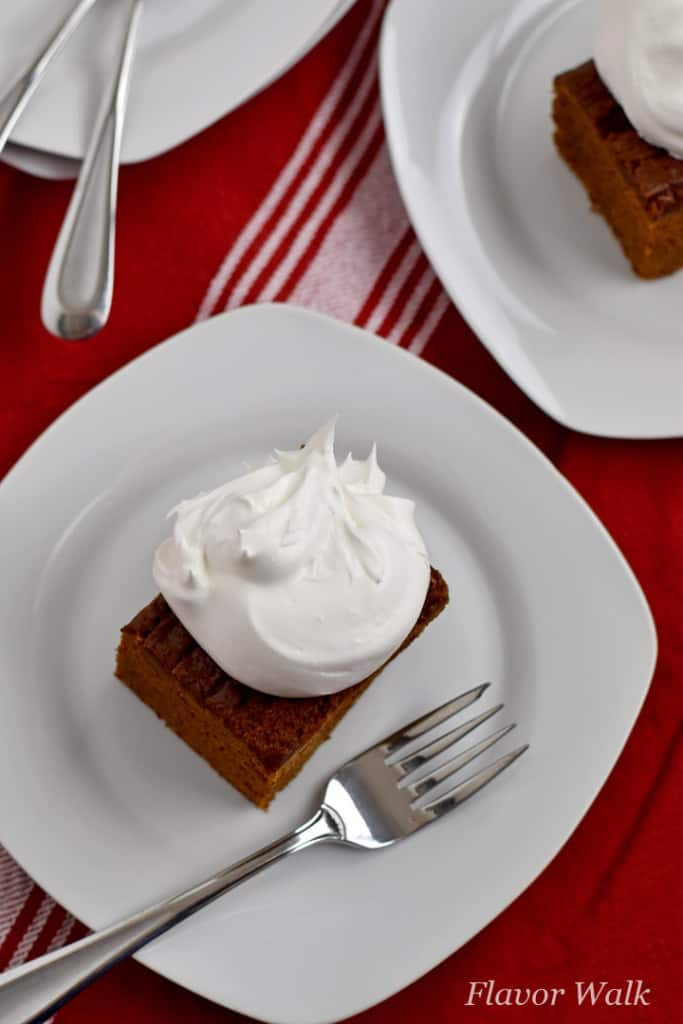 Overhead view of a slice of gluten free gingerbread cake, topped with whipped topping, and a fork on a small white plate sitting on a red and white striped kitchen towel. Additional forks, plates, and cake in the background.