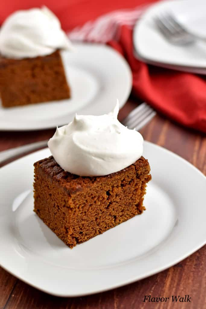 Close up view of a slice of gluten free gingerbread cake, topped with whipped topping, on a small white plate with additional cake, plates, and forks in the background.