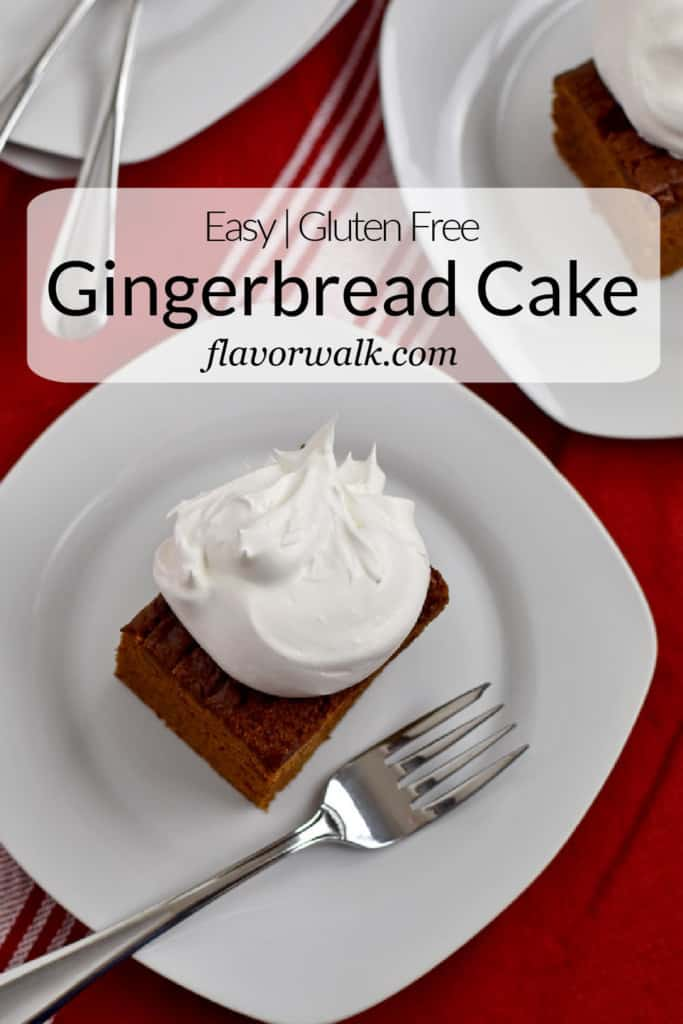 A piece of gluten free gingerbread cake topped with whipped topping and a fork on a small white plate with more cake in the background and a white and black text overlay near the top.