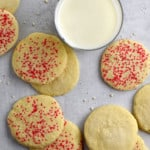Overhead view of a glass of milk and gluten free butter cookies scattered on parchment paper.