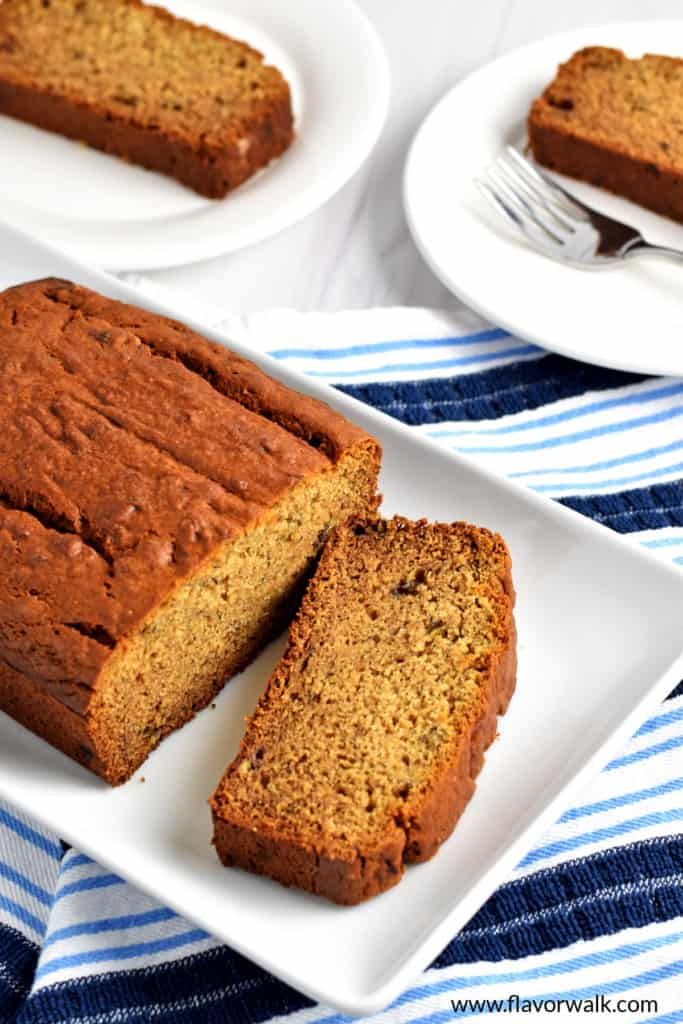 A loaf of gluten free peanut butter banana bread and one slice on a white rectangular serving plate sitting on a blue and white striped kitchen towel with more slices of the bread in the background.