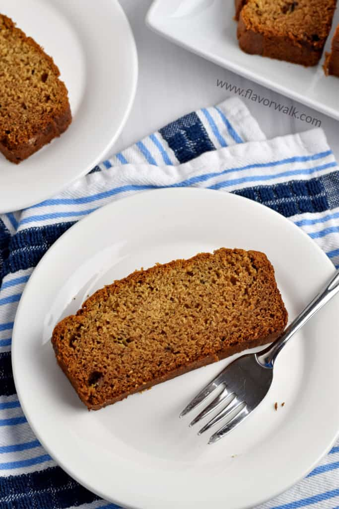 A slice of gluten free peanut butter banana bread and a fork on a round white plate sitting on a blue and white striped kitchen towel with another slice of bread on a small white plate and the remaining loaf in the background.