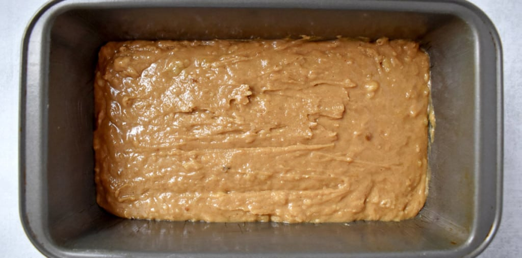 Overhead view of the batter for making gluten free peanut butter banana bread in a loaf pan.